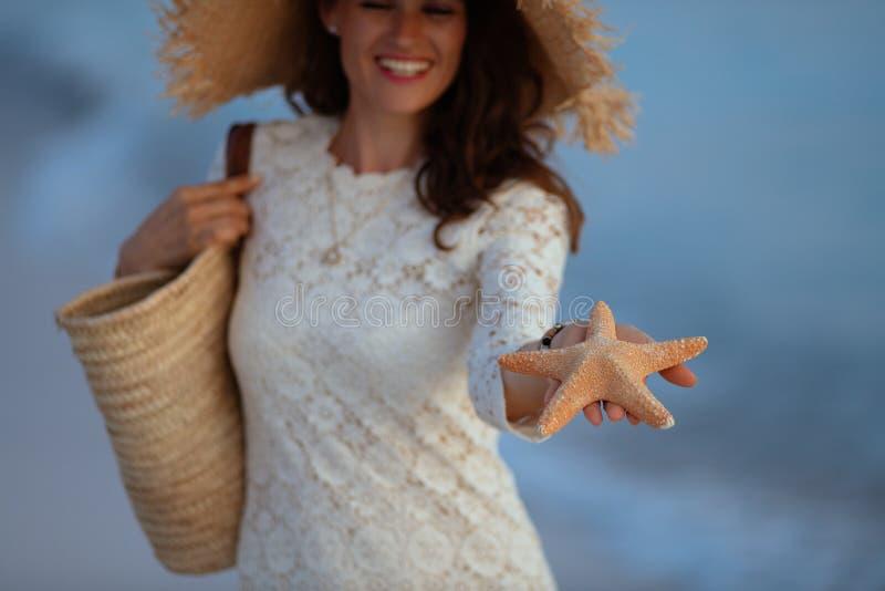 Closeup on woman on ocean coast at sunset showing starfish royalty free stock photos
