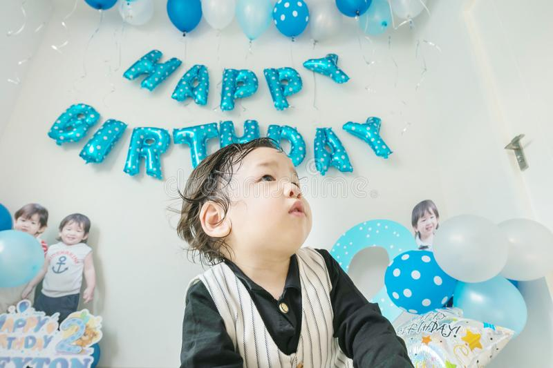 Closeup happy asian kid in room with birthday decoration in 2 nd years anniversary concept royalty free stock photo