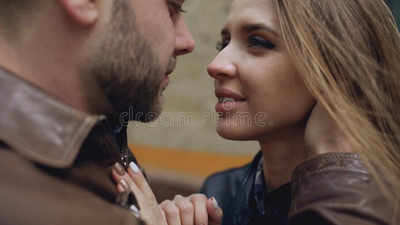 Closeup of happy loving couple kissing and embracing while havinhg walk in city street royalty free stock images