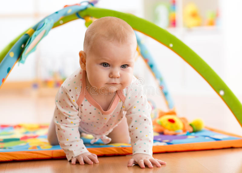 Closeup of happy seven months baby girl crawling on colorful playmat royalty free stock photos
