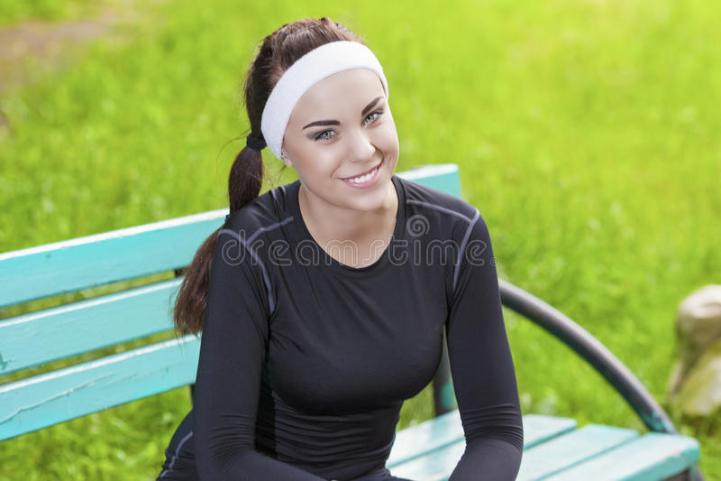 Closeup of Happy Smiling Caucasian Sportswoman in Fitness Jogging Gear Outdoors Prior to Her Running Training royalty free stock image