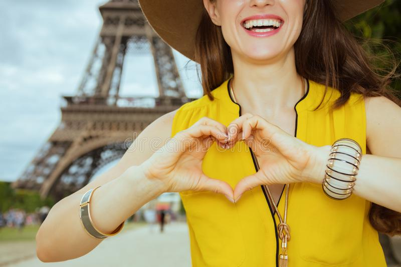 Closeup on happy traveller woman showing heart shaped hands. Closeup on happy modern traveller woman in yellow blouse and hat showing heart shaped hands against stock photo