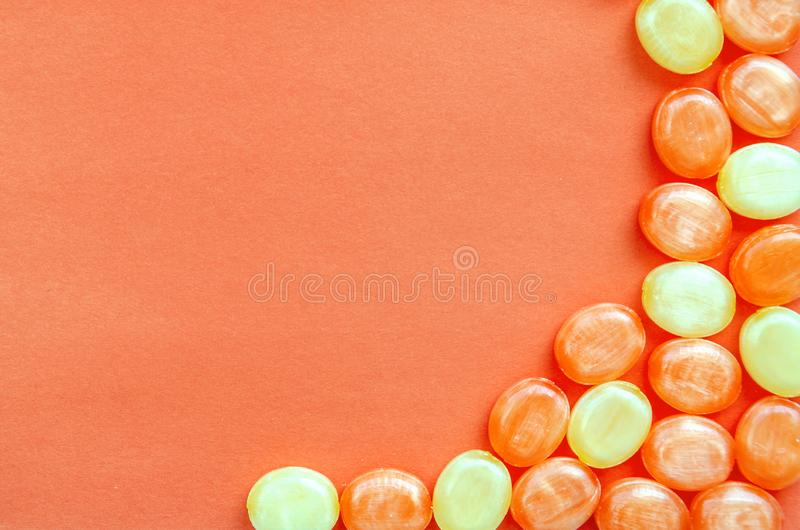 Closeup of hard sucking fruit candies on a coral background. Orange and lemon sweets. Copy space. Top view. Copy space royalty free stock image