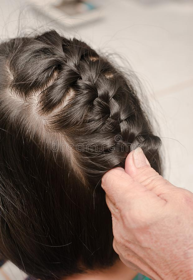 Closeup of head of asian kid. Grandmother is making of braids on little granddaughter`s royalty free stock photos