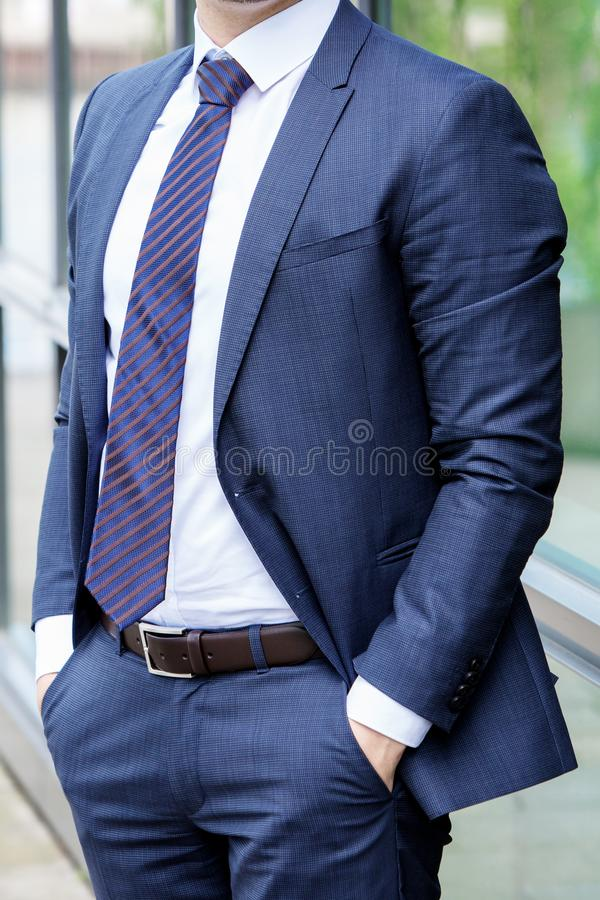 Headless businessman in a blue suit standing outdoor royalty free stock images
