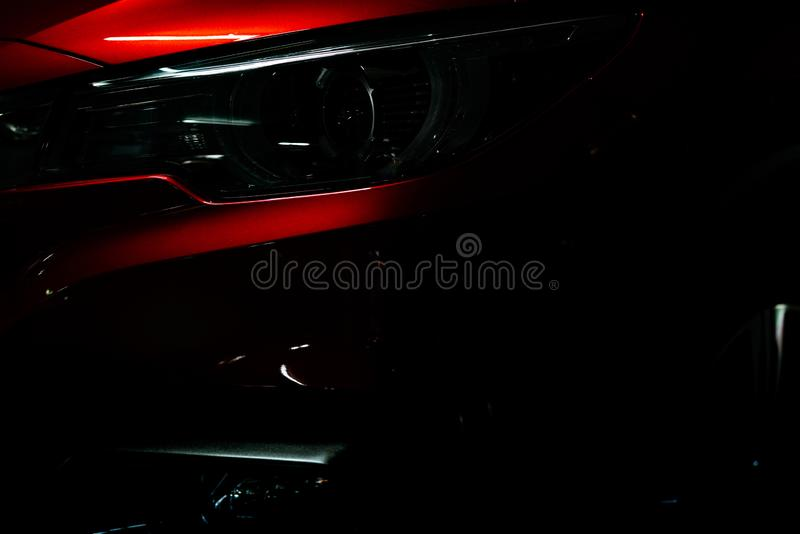 Closeup headlight of shiny red luxury SUV compact car. Elegant electric car technology and business concept. Hybrid auto stock images