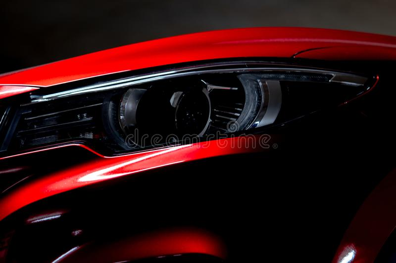 Closeup headlight of shiny red luxury SUV compact car. Elegant electric car technology and business concept. Hybrid auto royalty free stock photography