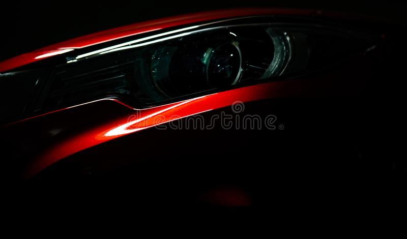 Closeup headlight of shiny red luxury SUV compact car. Elegant electric car technology and business concept. Hybrid auto stock photography
