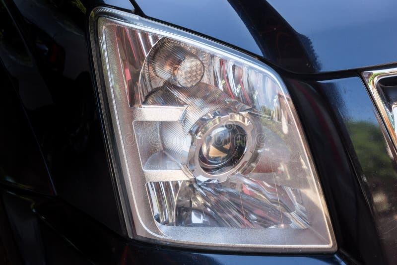 Closeup headlights of modern black car royalty free stock images