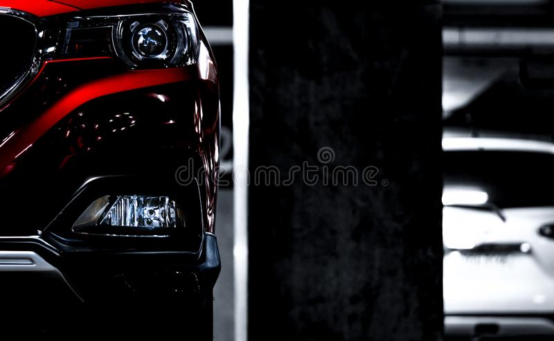 Closeup headlights of red SUV sport car parked near concrete pole at indoor parking lot. Headlamp lights with elegant and luxury royalty free stock image