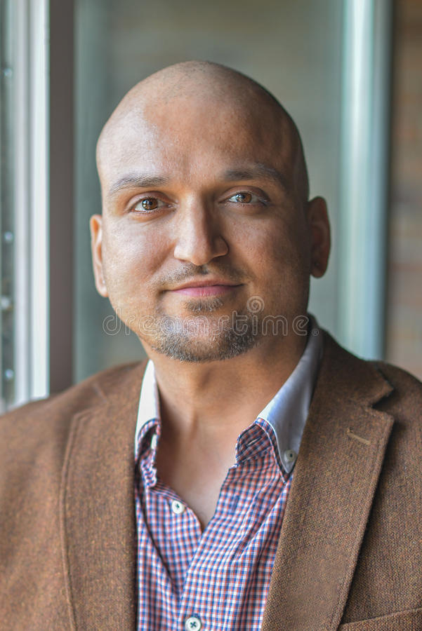 Closeup headshot portrait, happy handsome indian business man, smiling, confident and friendly indoors. stock image