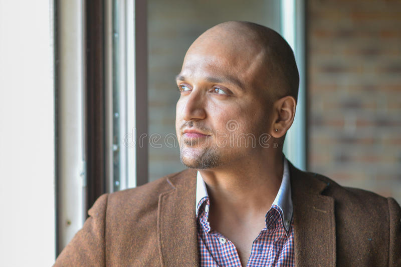 Closeup headshot portrait, happy handsome indian business man, smiling, confident and friendly indoors. royalty free stock photo