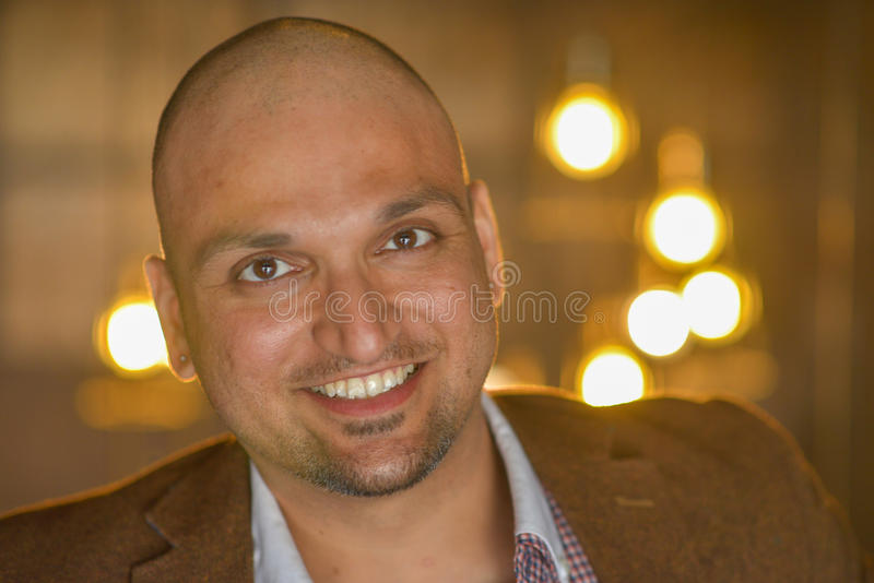 Closeup headshot portrait, happy handsome indian business man, smiling, confident and friendly indoors. stock photography