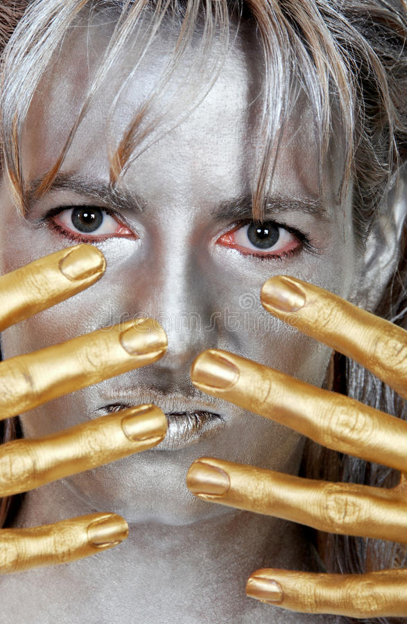Closeup headshot silver woman with gold fingers stock image