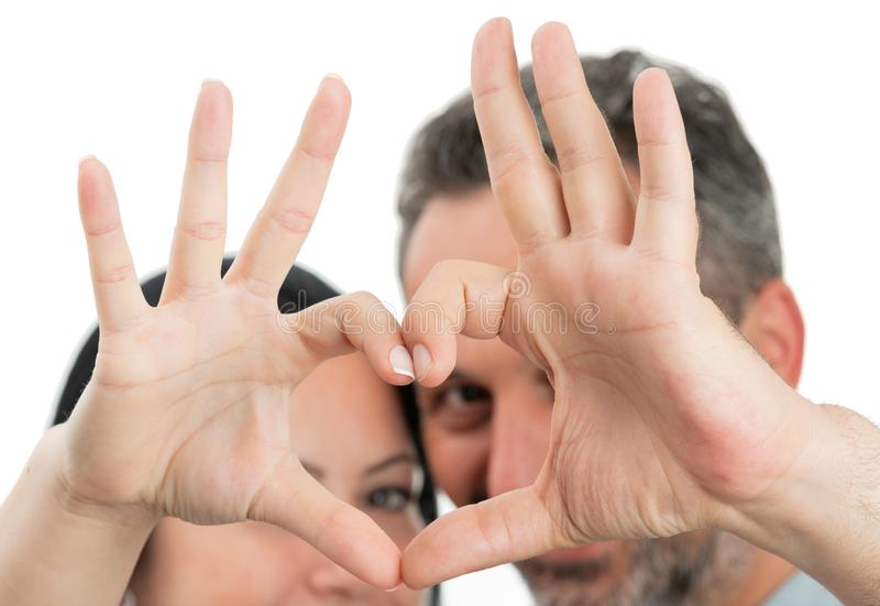 Closeup of heart gesture made by couple. Closeup of heart gesture made with fingers by man and woman couple as relationship concept isolated on white stock photo
