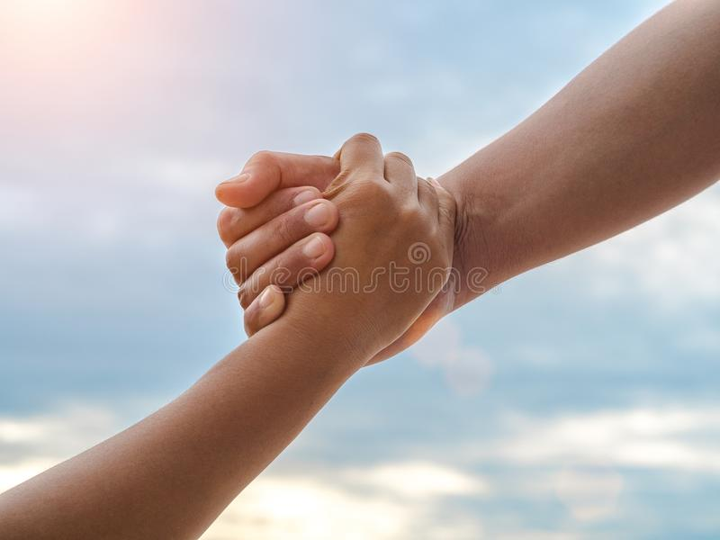 Closeup helping hands on the sky background. Rescue & Help Cencept royalty free stock photography