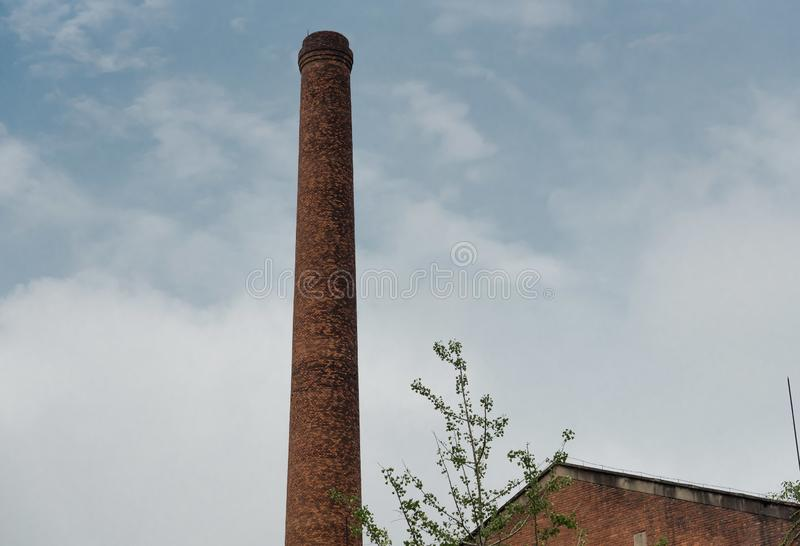 High industry chimney with blue sky. Closeup of high industry chimney of a factory with blue sky and withe coulds royalty free stock photo