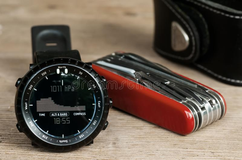 Closeup of hiking wrist watch and multipurpose knife on wooden table royalty free stock photography