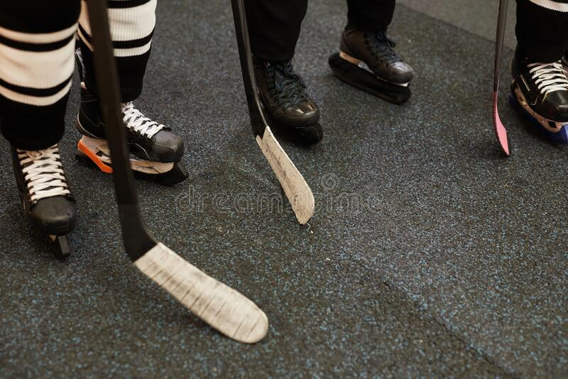 Closeup of Hockey Team Before Match. Background image of hockey team players ready for match in locker room, closeup shot of skating shoes and hockey clubs, copy stock photography