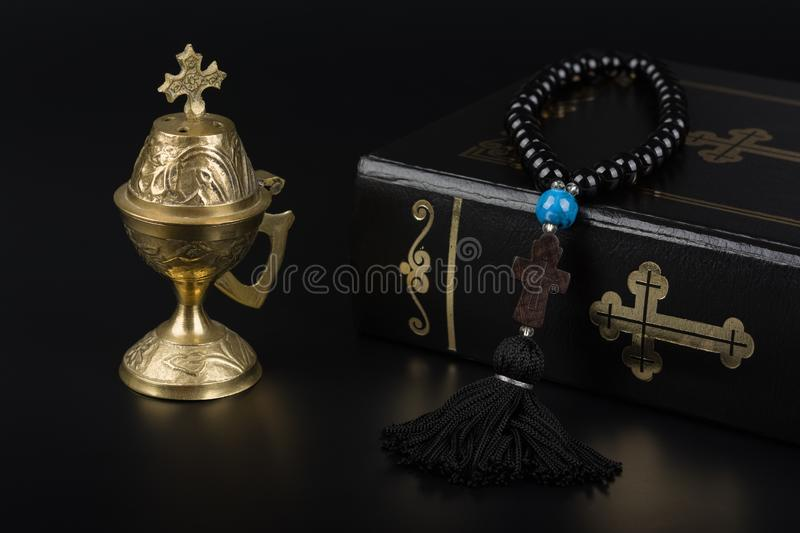 Closeup of Holy Bible, rosary beads with cross and incense burner on black background. Religion concept and faith.  royalty free stock photography
