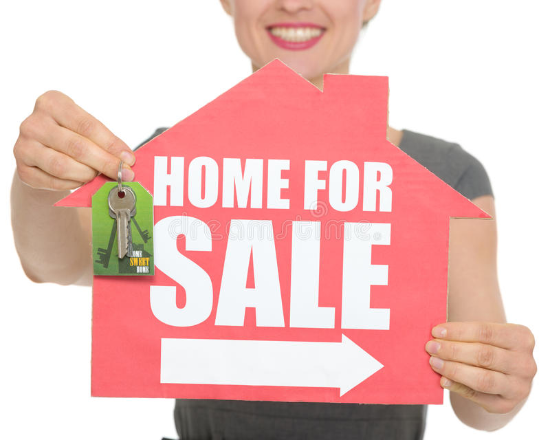 Closeup on home for sale sign and keys. Holding by happy female. HQ photo. Not oversharpened. Not oversaturated stock images