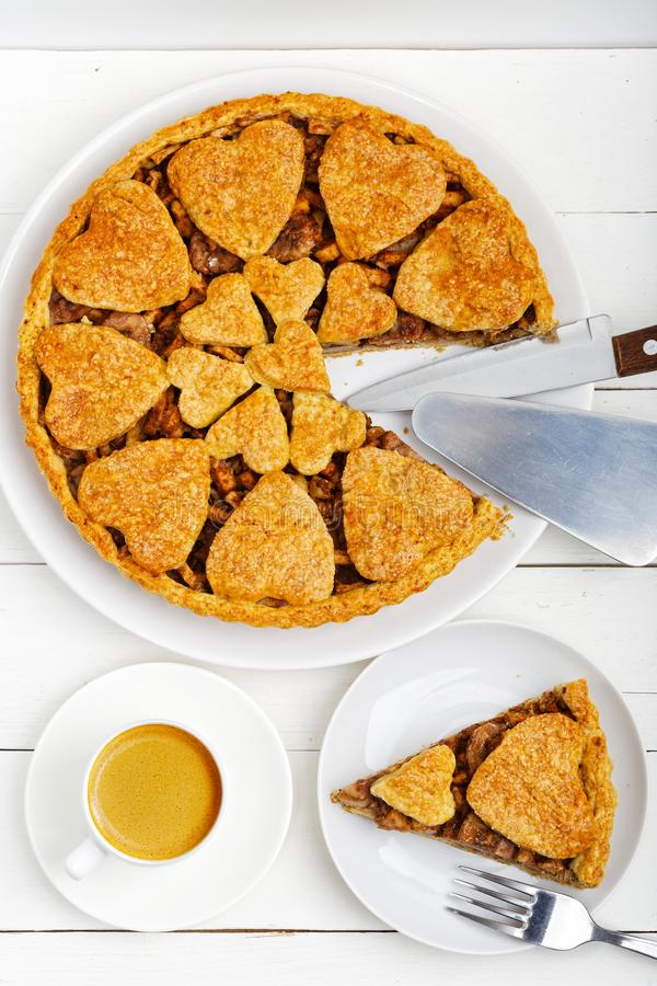 Closeup homemade apple pie with cinnamon and cup of coffee on white wooden table stock photo