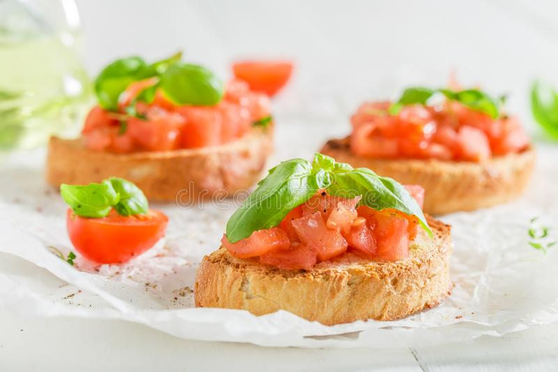 Closeup of homemade bruschetta with tomato and basil royalty free stock photography