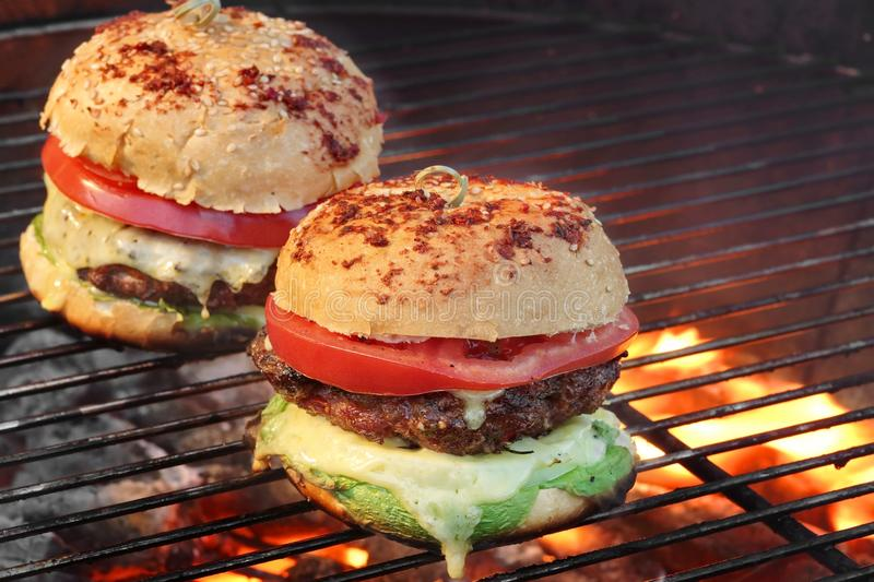 Closeup of Homemade Burgers On Hot BBQ Grill royalty free stock photos