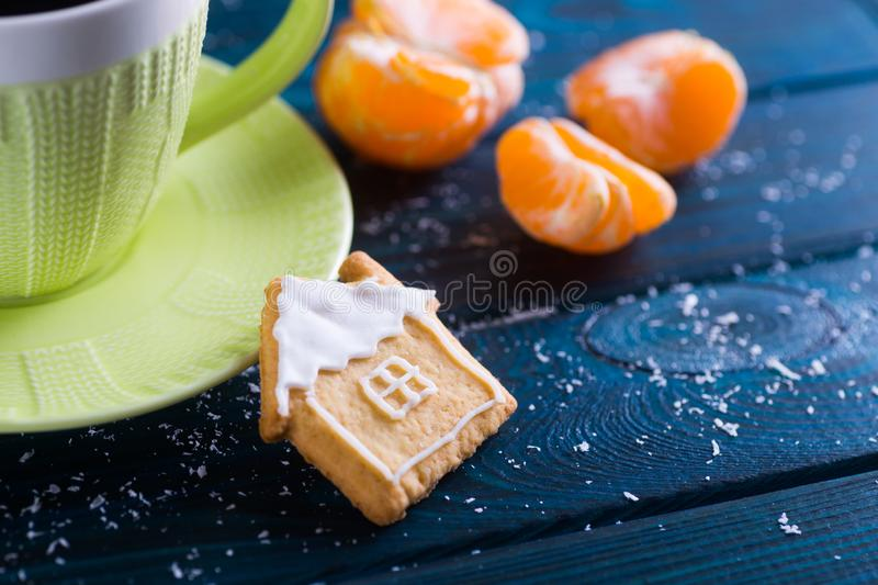 Closeup homemade Christmas glazed cookie in form of cute house on table with cup of coffee and mandarins. stock image