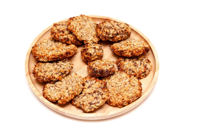 Closeup homemade natural oatmeal dietary lean cookies with seeds on a round wooden plate isolated on a white background. The stock photo