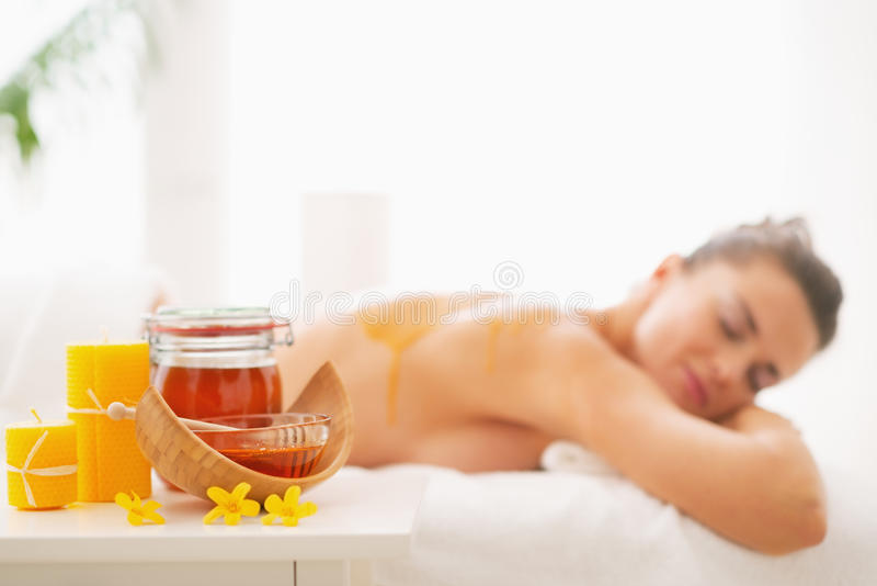 Closeup on honey spa therapy ingredients and woman in background. Closeup on honey spa therapy ingredients and young woman in background stock photography