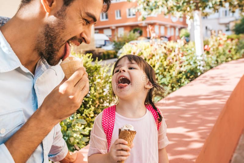 Closeup horizontal portrait of cute little girl sitting with dad on the city street and eating ice-cream outdoor. Happy kid girl. Wears pink dress spending time stock photos
