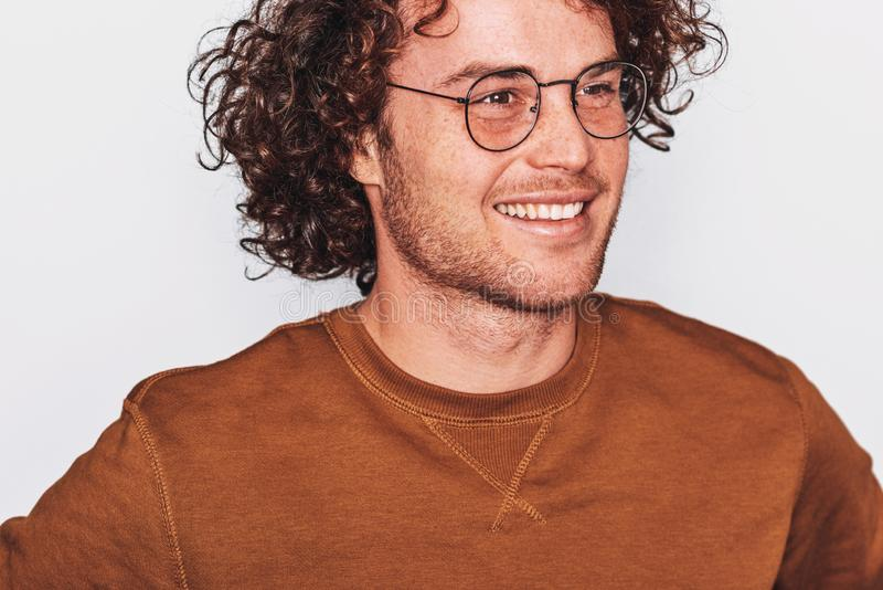 Closeup horizontal portrait of handsome smiling young male with curly hair, wears brown pullover and round trendy spectacles royalty free stock images