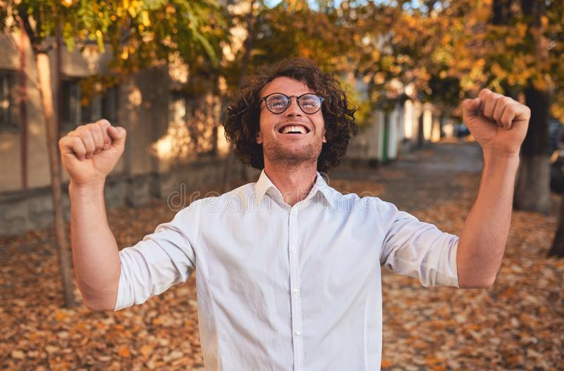 Closeup horizontal portrait of happy winner male student or businessman with curly hair smiling with winning expression, fists royalty free stock image