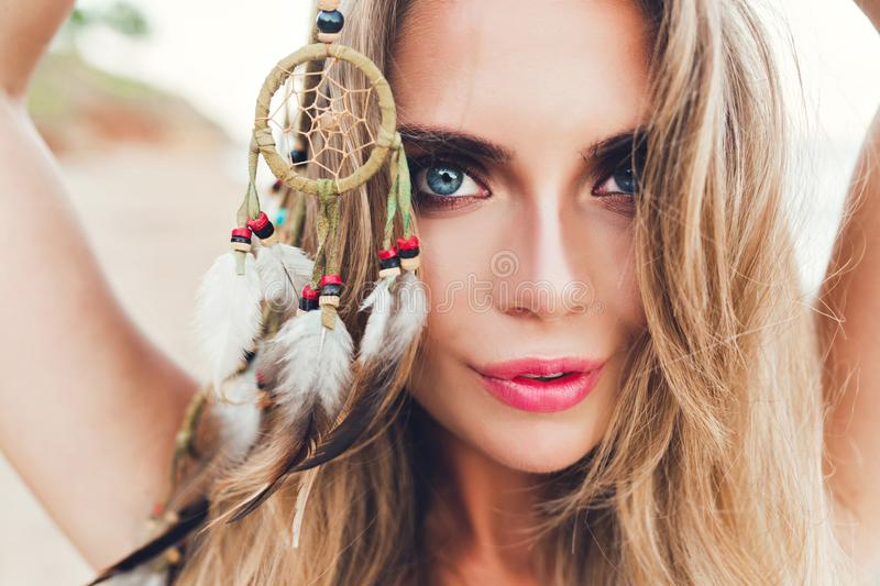 Closeup horizontal portrait of pretty blonde girl with long hair on beach. She holds ornamentation with feathers in hand. Closeup horizontal  portrait of pretty royalty free stock photo