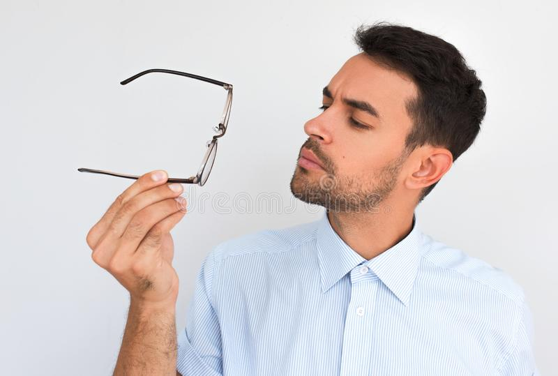Closeup horizontal portrait of unshaven handsome serious male touches rim of spectacles decide to wear, posing against white stock photo