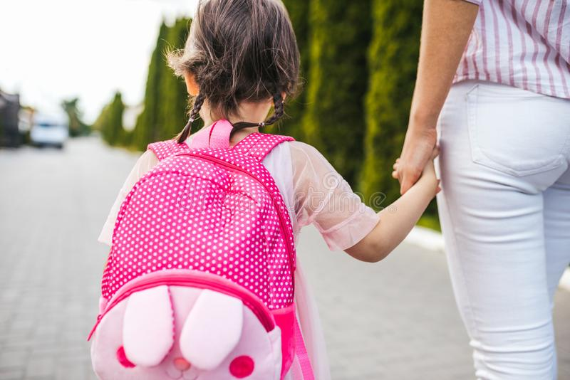 Closeup horizontal rear view of mother and little girl preschooler eith backpack go hand in hand to the kindergarten. Mom and her stock image