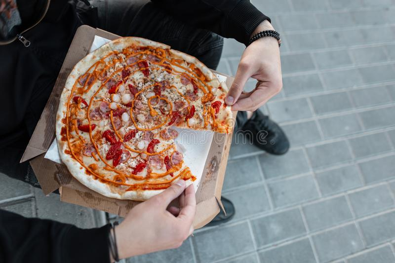 Closeup hot delicious pizza with sausage with cheese and tomatoes in the hands of a man in black stylish clothes. Guy is holding a pizza. Dinner time. View royalty free stock photography