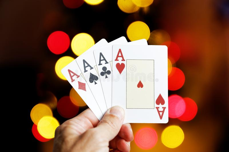 Closeup human hand holding four playing cards aces. Against colorful lights on blurred background royalty free stock photos