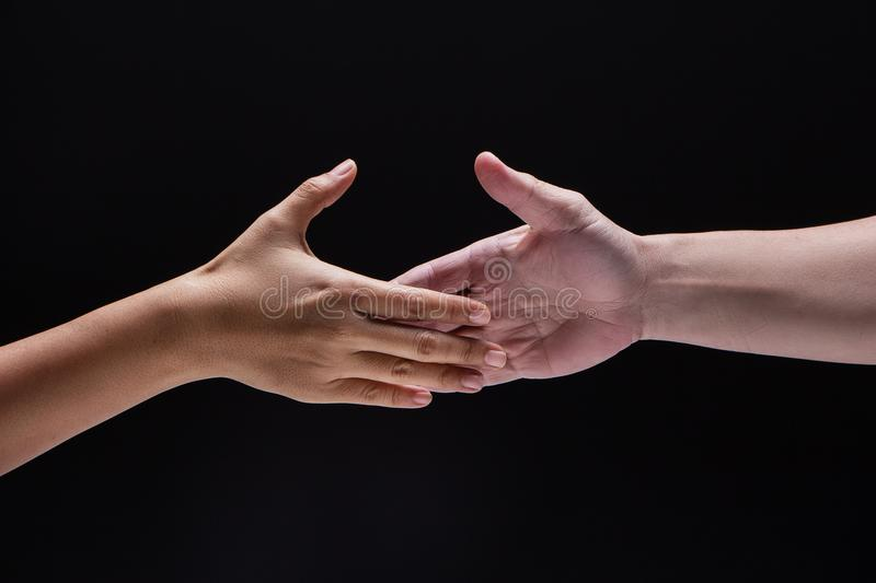 Closeup human hand ,between mand and woman.they are reaching to touch together,the sign and symbol of friendship. Collaborate,trust and love stock images