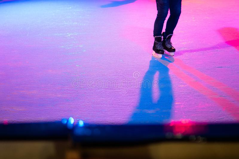 Closeup of human legs in old skates on outdoor public ice rink. Young figure skating on frozen lake in snowy winter park at night.  royalty free stock photography