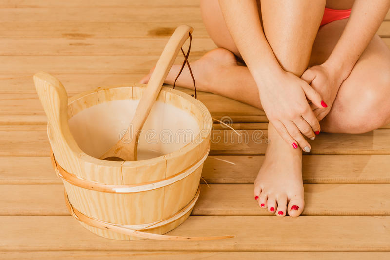 Closeup human woman legs feet and sauna bucket. royalty free stock photography