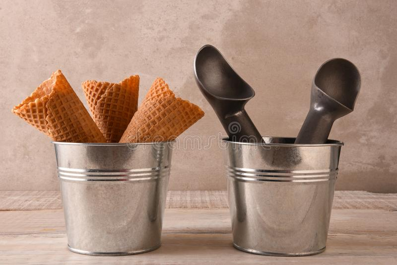 Closeup of ice cream cones in a small metal bucket next to a pail with two scoops. Closeup of three ice cream cones in a small metal bucket next to a pail with royalty free stock images