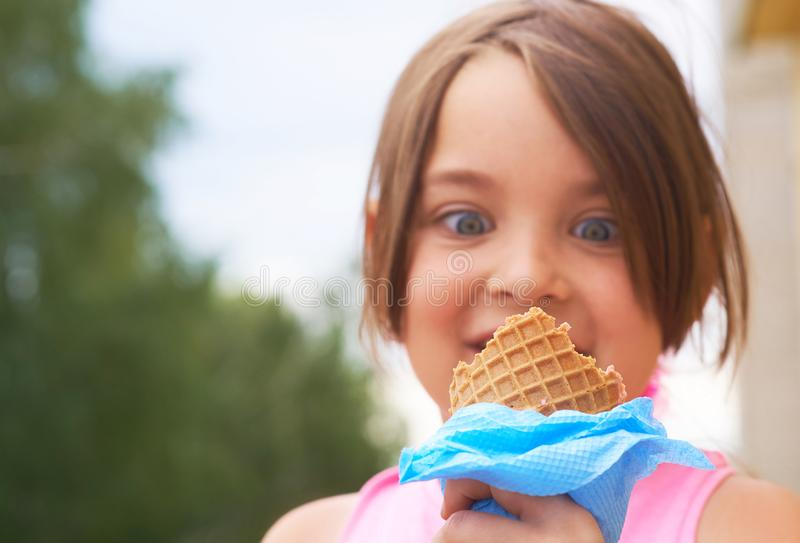 Closeup of ice cream held in hand by cute young girl. Little Caucasian girl eating ice cream in a waffle cone. royalty free stock images