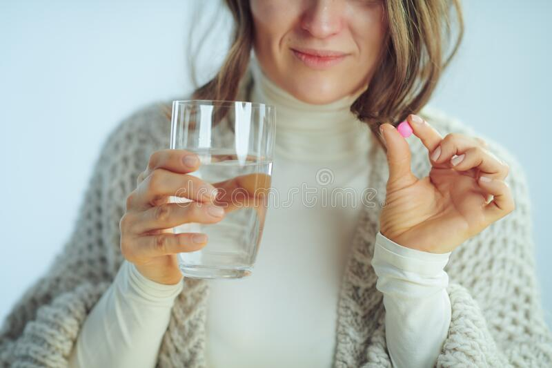 Closeup on ill modern housewife with cup of water showing pill. Closeup on ill modern 40 years old housewife in roll neck sweater and cardigan with cup of water stock photography