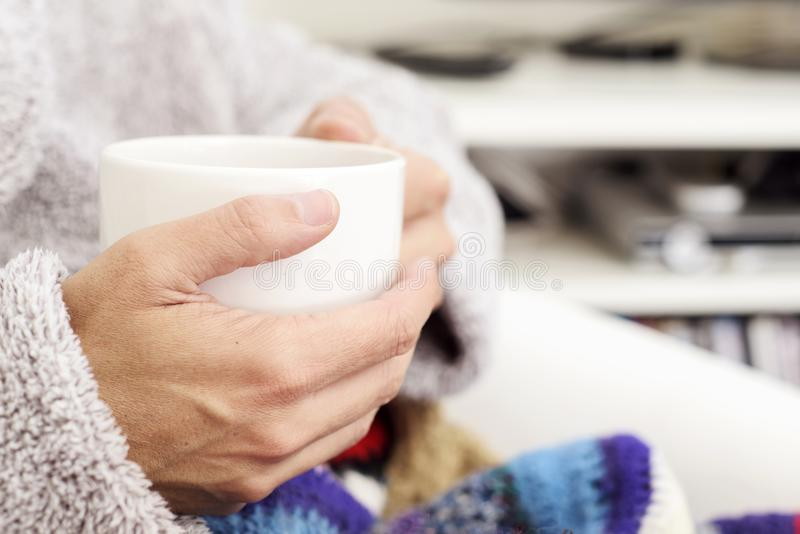 Ill man warming up with a cup of soup or hot tea royalty free stock photos