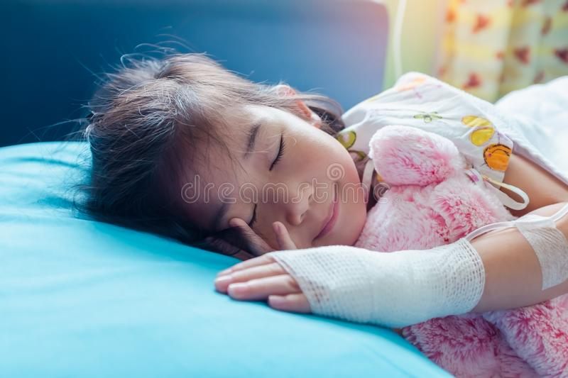 Illness asian child admitted in hospital with saline intravenous on hand stock images