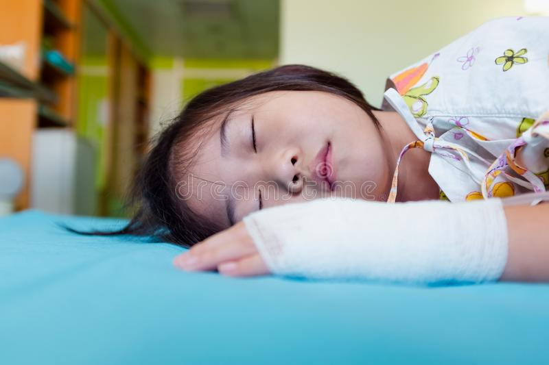Illness asian child admitted in hospital with saline intravenous on hand stock photos