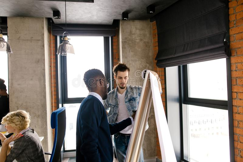 Afro businessman putting his ideas on flipping sheet of the board royalty free stock photos