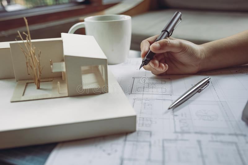 Closeup image of architects drawing shop drawing paper with architecture model. On table stock photography